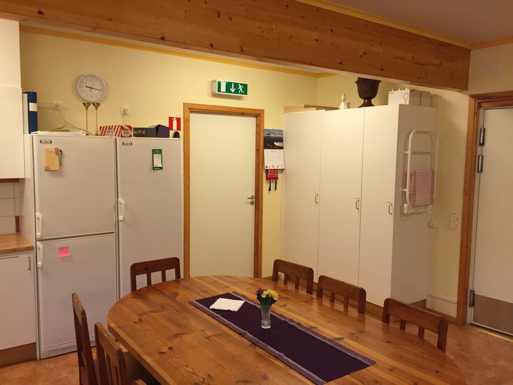 Till vänster kylskåp, till höger skåp med porslin.